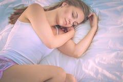 Eine schöne junge Frau bequem und, die himmlisch im Bett liegt stockfotos