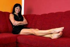 Eine schöne junge Frau, die auf dem Sofa sich entspannt Lizenzfreie Stockfotografie