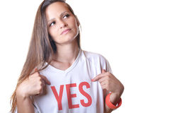 Eine schöne junge Frau, die auf Wort auf ihrem weißen t-shir zeigt Lizenzfreies Stockbild