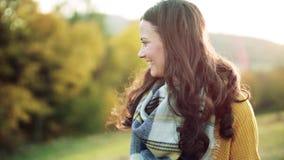 Eine sch?ne junge Frau, die in Herbstnatur geht Langsame Bewegung stock video footage