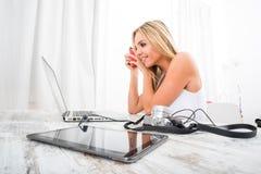 Eine schöne junge Frau an einem Tisch Lizenzfreie Stockfotografie