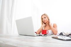 Eine schöne junge Frau an einem Tisch Lizenzfreies Stockbild
