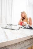 Eine schöne junge Frau an einem Tisch Stockfotografie
