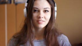 Eine schöne junge Frau in einer Bibliothek beim Hören Musik mit den Kopfhörern und Tagträumen, die zur Musik tanzen stock video footage