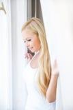 Eine schöne junge Frau im Fenster Lizenzfreies Stockbild