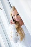 Eine schöne junge Frau im Fenster Stockfotos