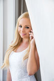 Eine schöne junge Frau im Fenster Lizenzfreie Stockfotografie