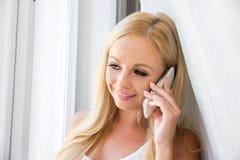 Eine schöne junge Frau im Fenster Stockfotografie