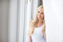Eine schöne junge Frau im Fenster Stockbild