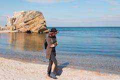 Eine schöne junge Frau macht einen entspannenden Spaziergang entlang einem sandigen Strand Lizenzfreie Stockbilder