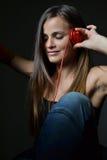 Eine schöne junge Frau mit den roten Kopfhörern lizenzfreie stockfotos