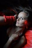 Eine schöne junge Frau mit den roten Kopfhörern Lizenzfreies Stockbild