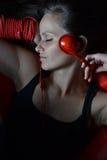 Eine schöne junge Frau mit den roten Kopfhörern stockfoto