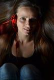 Eine schöne junge Frau mit den roten Kopfhörern Stockfotos