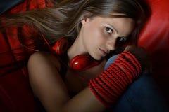 Eine schöne junge Frau mit den roten Kopfhörern Lizenzfreie Stockbilder