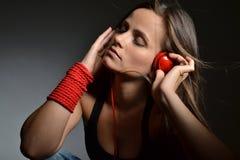 Eine schöne junge Frau mit den roten Kopfhörern lizenzfreies stockfoto
