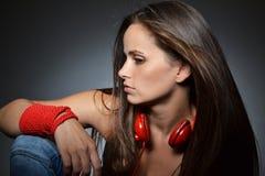 Eine schöne junge Frau mit den roten Kopfhörern stockbild