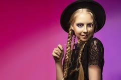 Eine schöne lächelnde blonde Jugendliche, die ein schwarzes gotisches d trägt Stockfotografie