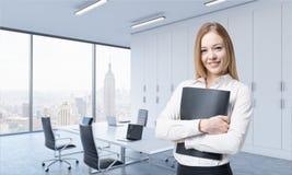 Eine schöne lächelnde Frau hält einen schwarzen Dokumentenordner im modernen panoramischen Büro stockbild