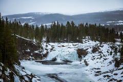 Eine schöne Landschaft eines gefrorenen Wasserfalls am Tag des verschneiten Winters Stockfoto