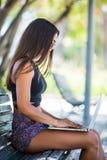 Eine schöne lateinische junge Frau in der Sonnenbrille, die auf Bank legt und draußen an Laptop arbeitet stockbilder