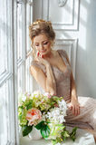 Eine schöne sinnliche junge blonde Frau in einem beige Kleid sitzt auf a Lizenzfreies Stockfoto