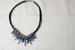 Eine schöne, weibliche, moderne Halskette auf einem schwarzen Gummiband mit blauen glänzenden Edelsteinen, Diamanten gegen ein be Stockfotos