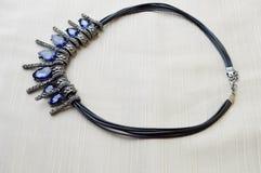 Eine schöne, weibliche, moderne Halskette auf einem schwarzen Gummiband mit blauen glänzenden Edelsteinen, Diamanten gegen ein be Lizenzfreie Stockbilder