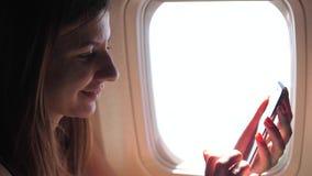 Eine Schönheit benutzt das Telefon und sitzt am Fenster der Fläche stock footage