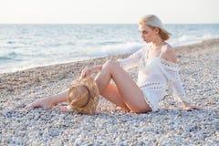 Eine Schönheit in einem weißen Badeanzug auf dem Strand-Ozean lizenzfreies stockfoto