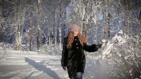 Eine Schönheit ist glücklich und geht in den Park an einem Wintertag stock video