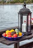 Eine Schüssel des Gemüses und der Kerzenlampe durch den See Lizenzfreies Stockfoto