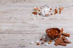 Eine Schüssel geschmolzene Milchschokolade mit Haselnüssen nahe bei in dem einem Glasdeckel ein Eibisch lizenzfreie stockfotos