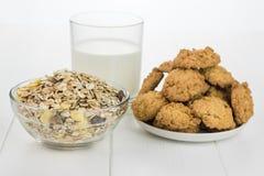 Eine Schüssel Getreide, Glas Milch und Plätzchen gemacht vom Weizenmehl Stockfoto