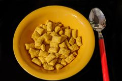 Eine Schüssel Getreide mit einem Löffel gegen einen schwarzen Hintergrund Stockfotografie