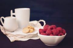 Eine Schüssel mit Himbeeren Tasse Kaffee, Plätzchen ein Krug Milch auf einem Strohbehälter Schwarzer Hintergrund Weinlese abgetön Lizenzfreies Stockbild