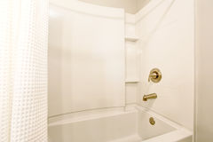 Eine Schüssel und ein Tuch Ansicht der weißen Badewanne und des weißen Duschvorhangs stockfotos