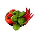 Eine Schüssel voll Tomaten, Pepperonis und Basilikum lizenzfreie stockfotografie