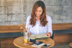Eine sch?ne asiatische Frau, die ein Buch beim Sitzen im Caf? h?lt und liest lizenzfreies stockfoto