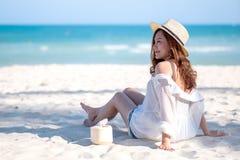 Eine sch?ne asiatische Frau genie?en, Kokosnusssaft auf dem Strand zu sitzen und zu trinken lizenzfreie stockfotos