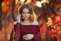 Eine sch?ne schwangere Frau mit dem blonden Haar im langen roten Kleid lizenzfreie stockbilder