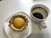 Eine Schale betrunkener Kaffee und Kuchen sind auf dem Tisch Stockfoto