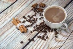 Eine Schale Cappuccino auf dem Tisch, nahe den Kaffeebohnen, Sternanis und einem Bündel Zimt Nahaufnahme lizenzfreie stockfotografie