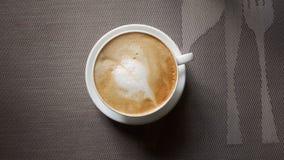 Eine Schale Cappuccino mit Blattdekoration stockbilder