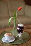 Eine Schale Cappuccino und ein Glas Klumpen mit Blaubeere stauen Stockbilder