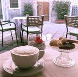 Eine Schale Capuccinokaffee auf einer äußeren Cafétabelle mit Blick auf eine ruhige Venedig-Straße Stockbild