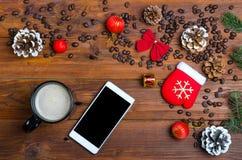 Eine Schale des heißen Getränks und des Mobiles auf einem Holztisch Stockbild