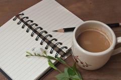 Eine Schale des heißen Kaffees, der Blumen und des Buches, romantischer Hintergrund Lizenzfreies Stockbild