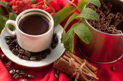 Eine Schale des heißen starken Kaffees, der Zimtstangen, der Kaffeebohnen und des Bündels Aschbeeren auf einem Rot drapierte Gewe Stockbild