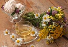 Eine Schale des Kamillenteen in einer Glasschale, der Schüssel Eibische und des Blumenstraußes des Feldsommers blüht auf einer Ho Lizenzfreies Stockfoto